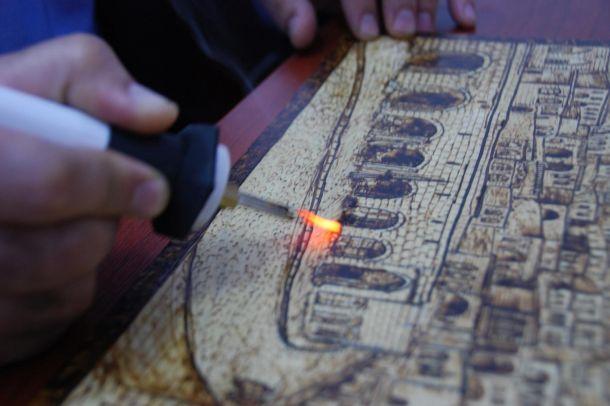 Ahşaba çizdiği resimlerle tarihi yansıtıyor