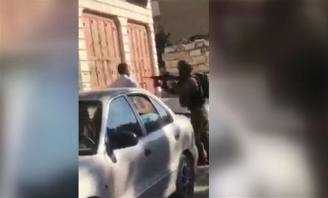 İşgal çetesi askeri Filistinli babaya çocuğunun önünde silah doğrulttu